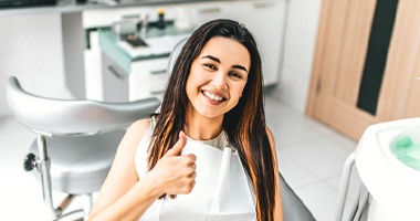 Woman smiling in dental chair with thumbs up
