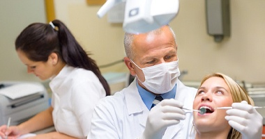 Dentist inspecting female patient's teeth during checkup