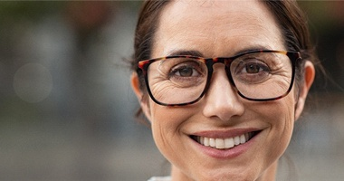 Woman in white shirt smiling with brown glasses