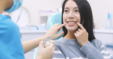 Woman pointing at tooth during a dental implant consultation