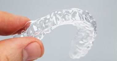 A person holding a clear aligner.