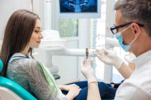 Denist showing patient dental implant post