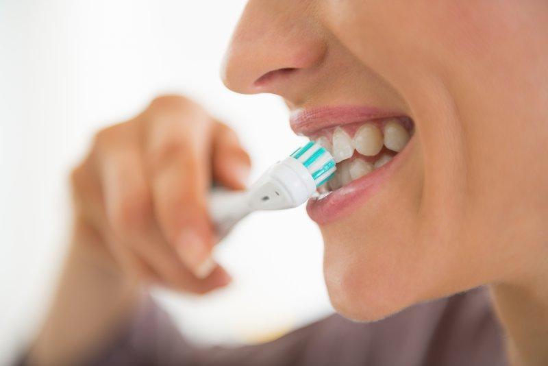 Woman brushing her teeth.