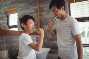 parent brushing their teeth with child