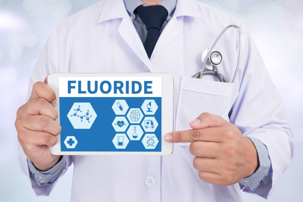 A dentist promoting cavity prevention holds a sign that reads, Fluoride