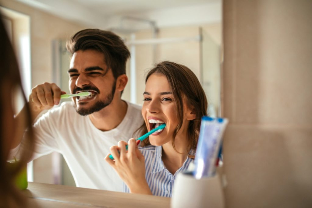 Couple brushing their teeth trying to avoid trips to the emergency dentist