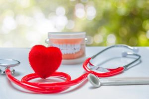Heart shape, stethoscope, and teeth model sit next to Medford dentist equipment