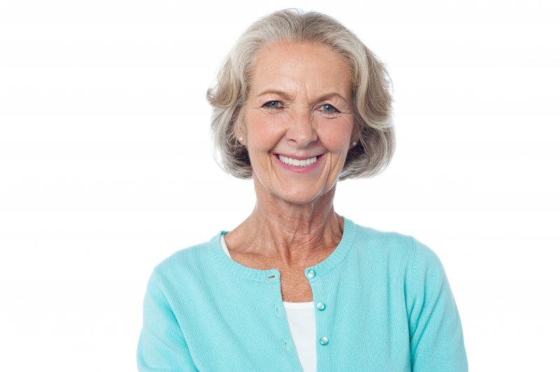 an older woman wearing a teal cardigan and showing off her healthy, beautiful smile thanks to dental implants