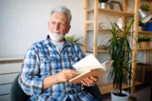 man reading a book learning about the evolution of dentures